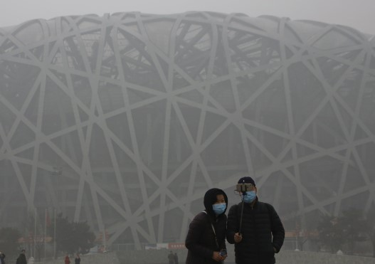 Visitors wearing protective masks take a selfie in front of the National Stadium in Beijing